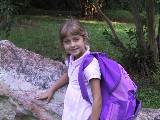 malá holčička v bílých šatech a s fialovým batohem